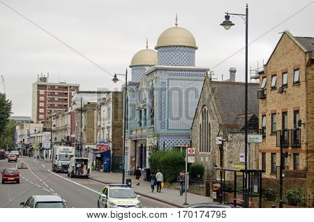 LONDON UK - SEPTEMBER 17 2016: Traffic and pedestrians on the busy Stoke Newington Road with the landmark Aziziye Mosque covered in beautiful blue tiles. Viewed on a cloudy Saturday afternoon in Hackney London UK.