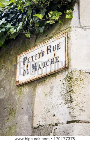 Old French street sign Petite Rue Du Marche or Market alley on an old limestone wall Ile de Re France