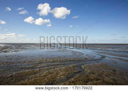 Maritime landscape with reflection of clouds in low tide water Waddenzee Friesland The Netherlands
