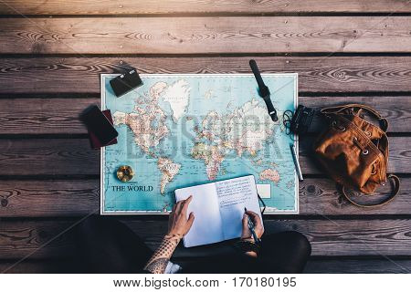 Young woman making notes in diary looking at the world map with travel accessories around. Tourist planning vacation using a world map.