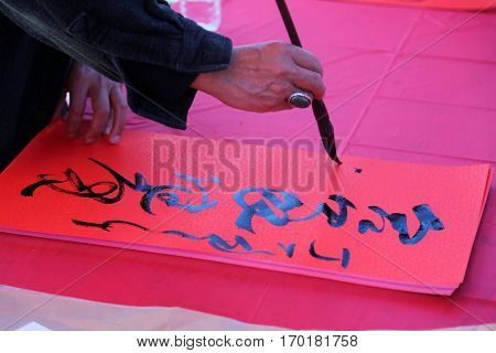 MONTERY PARK, CALIFORNIA JANUARY 28, 2017: - A person writes a fortune in Chinese calligraphy reading Year of the Chicken at a Lunar New Year Celebration.