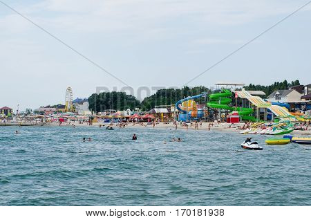 ZALIZNY (ZHELEZNY) PORT UKRAINE - 29 AUGUST 2016: View on sea quay and sandy beach with people having rest sunbathing and swimming