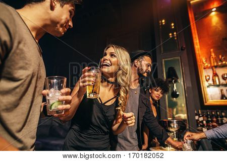 Group of young people having fun at nightclub. Young friends enjoying a night at bar.