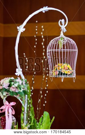 white Birdcage with flowers inside, The decoration in a wedding ceremony