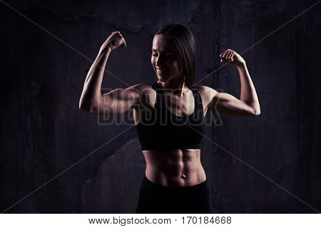 Indoors shot of young confident muscular woman showing the relief of abdomen. Strong and powerful young woman showing perfect body