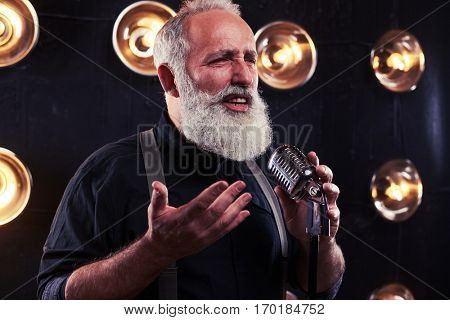 Mid-length shot of exhilarated male singer in a dark holding a silver studio microphone. Using studio microphone and posing at the camera