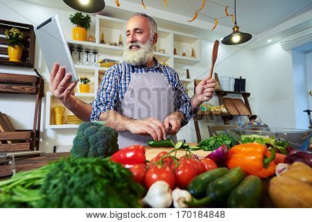 Funny shot of a multi-functional chef with many hands preparing food, with tablet and wooden spoon. Happy chef preparing vegetable salad in the kitchen