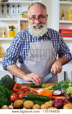 Close-up of smiling mature man. Bearded man wearing glasses posing at the camera while preparing a vegetable salad. Positive bearded man trying to prepare a healthy breakfast