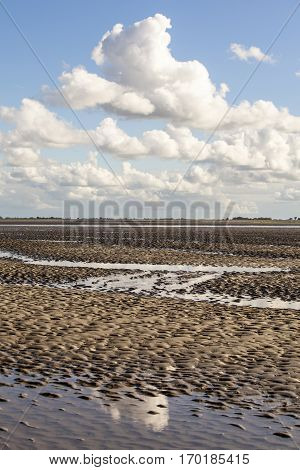 Maritime landscape with reflection of white clouds in low tide water Waddenzee Friesland The Netherlands