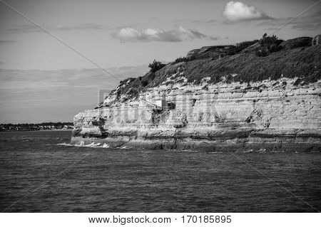 Black and white view from the Gironde estuary with the limestone cliff of the village of Meschers sur Gironde and its troglodytic houses and traditionnal typical wooden fisherman cabins Charente maritime France