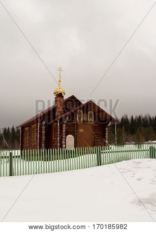 Verkhniy Tagil, Russia - 11.07.2016: Small wooden Church standing in snow behind green fence near forest.