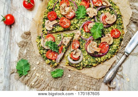 Kale oats pizza crust with tomato red onion and mushrooms.