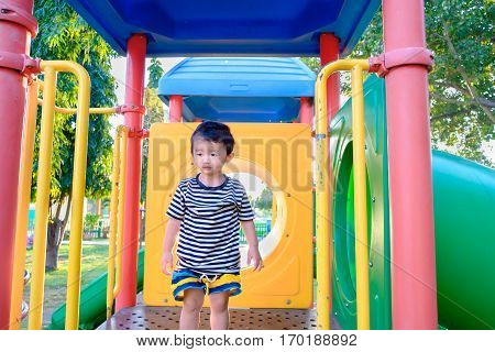 Sad Little Asian Kid On Slide At The Playground At The Day Time