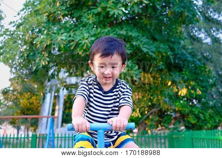 Asian Kid Riding Seesaw Board At The Playground Under Sunlight,