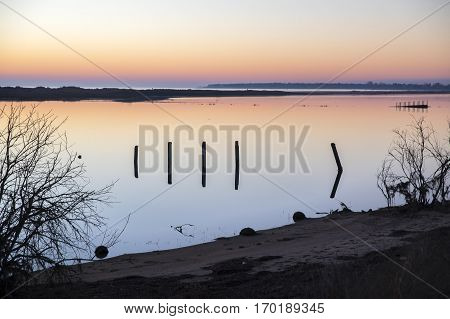 seaside landscape at sunset with reflection in still water over nature reserve Casse de la Belle Henriette, l'Aiguillon sur Mer,  Vendee, France