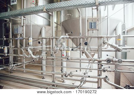 Modern beer plant, with brewing kettles, vessels, tubs and pipes made of stainless steel. Brewery.