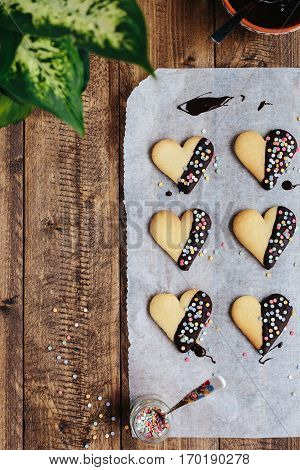 Heart Shaped Biscuits Dipped in Chocolate and Decorated with Colorful Sprinkles on Rustic Wooden Table