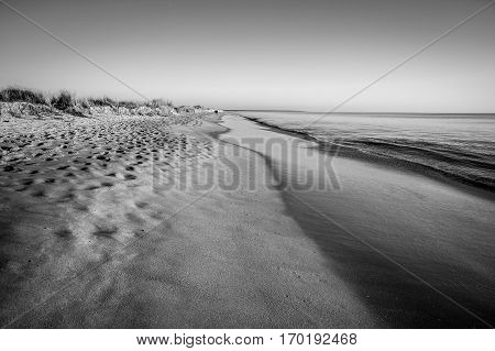Black and white view on a quiet beach and tranquil sea