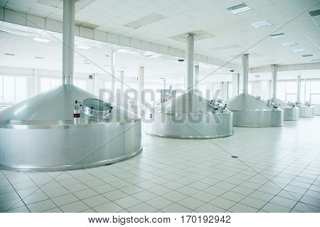 Brewing production - metal beer tanksin a spacious hall. Brewery.