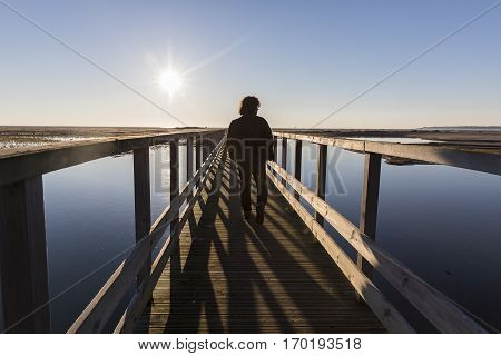 Backlit silhouette of a man walking on a wooden pontoon over a lagoon at sunset, Nature reserve Casse de la Belle Henriette, l'Aiguillon sur Mer