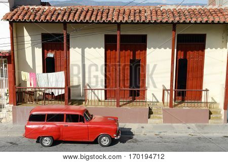 Santiago de Cuba, Cuba - 13 january 2016: old car in front of colonial houses at Santiago de Cuba, Cuba