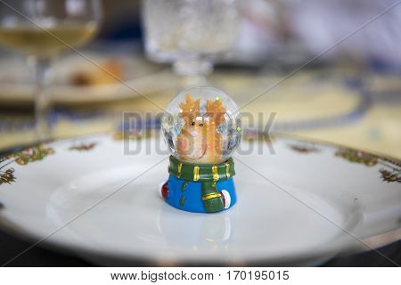Christmas table decorated with little reindeer figurine in glitter snowball