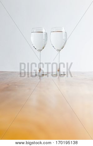 Two isolated wine glasses filled with clear liquid on a wooden table