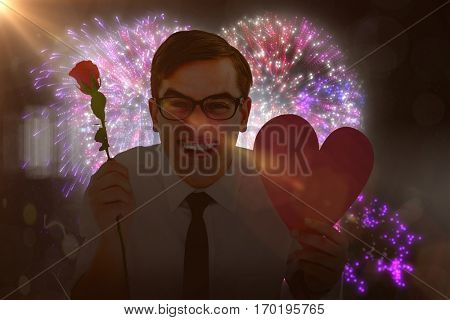 Geeky hipster holding a red rose and heart card against colourful fireworks exploding on black background