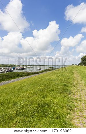 Grass dike in Friesland with blue sky with white clouds