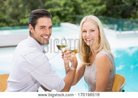 Portrait of smiling couple drinking wine at poolside