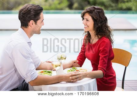 Smiling couple holding hands while sitting at poolside