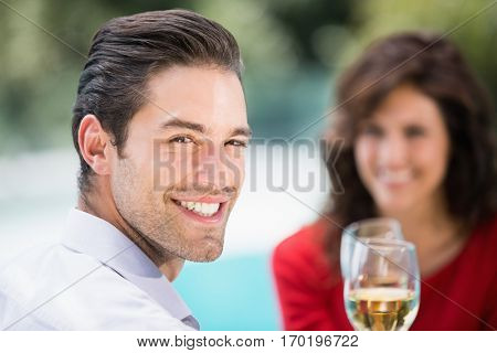 Close-up portrait of young man toasting white wine while sitting at poolside