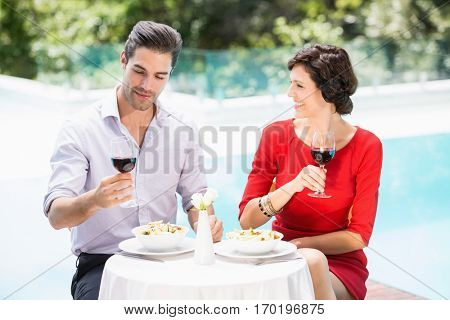 Couple holding red wine glasses while sitting at poolside