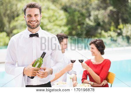 Portrait of smiling waiter holding wine bottle with couple sitting on background