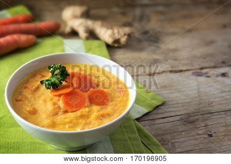 Carrot soup with ginger root parsley garnish and green napkin on a rustic wooden table with copy space selected focus narrow depth of field