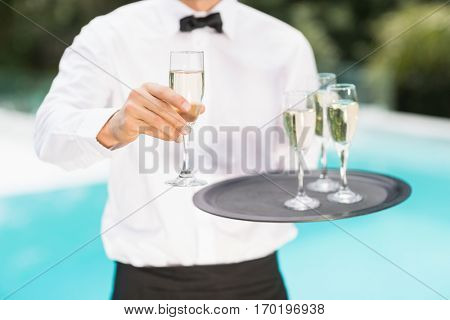 Midsection of waiter offering champagne at poolside