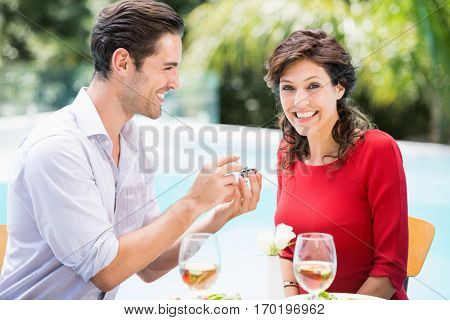 Portrait of smiling woman while receiving giving engagement ring from man