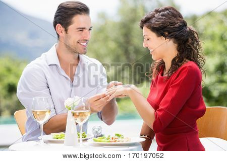 Smiling man wearing engagement ring to woman while sitting at poolside