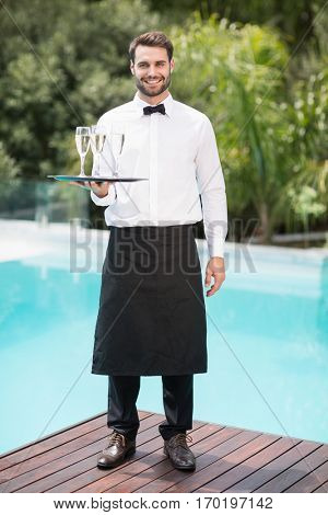 Full length portrait of smiling waiter carrying champagne flutes on tray at poolside