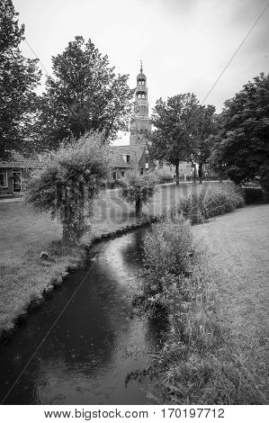 Balck and White view of a Dutch village with a canal and church bell tower, The Netherlands
