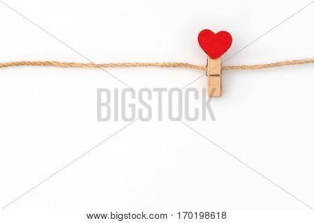Red paper heart hanging on white background