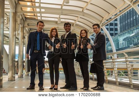 Five asian business teamwork with a group of people with a smile and a thumbs-job success.