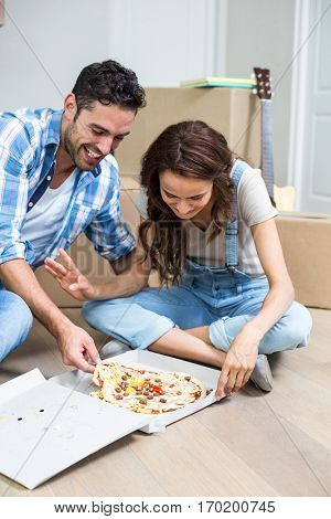 Happy couple having pizza while sitting in new house