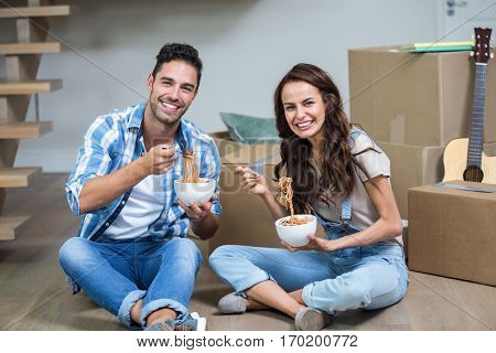Portrait of Smiling couple having noodles while sitting in new house