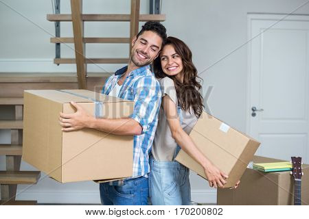 Happy couple with boxes at home