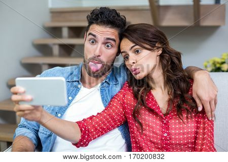 Couple making faces while taking selfie at home