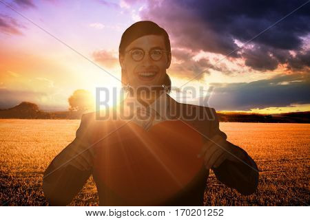 Geeky businessman smiling and holding heart card against countryside scene
