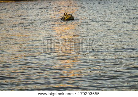 buoy for mooring ships in the middle of the river in the light of the setting sun