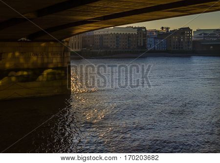 view from the underside of the famous bridge in London on buildings across the river london bridge the rays of the sun reflecting off the surface of the water