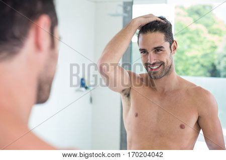 Handsome shirtless young man smiling while looking in mirror at bathroom